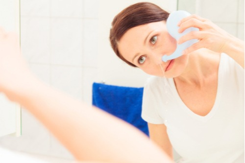 Photo Shows A Woman Using A Neti Pot To Perform Sinus Irrigation in Kirkland, Bellevue, and Seattle